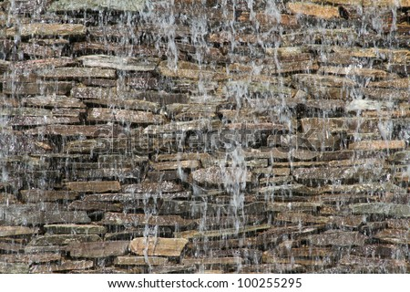 stone wall with a waterfall - stock photo