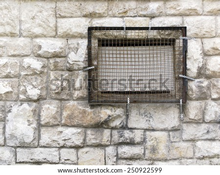 Stone wall with a windowwith grid