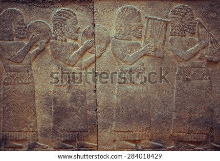Stone wall with ancient musicians, who is playing on antique musical instruments. Relief with assyrian musical scene - art and culture of Mesopotamia and Babylonia, Istanbul museum. - stock photo