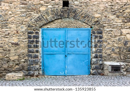 stone wall with arch and blue metall door - stock photo