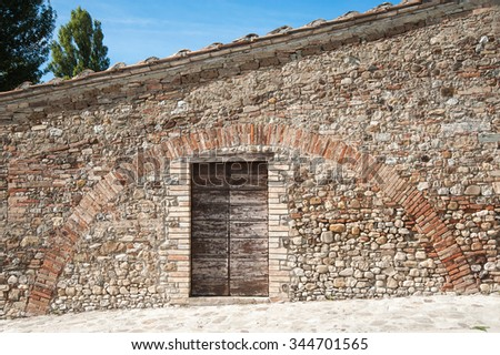 Stone wall with rounded cobbles and some red bricks with red brick arch over double wooden door in blockwork frame, traces of old roofline below terracotta tiled roof and blue sky - stock photo