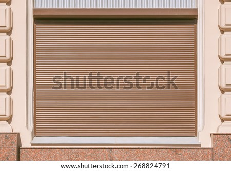 Stone wall with the roller shutter window. - stock photo