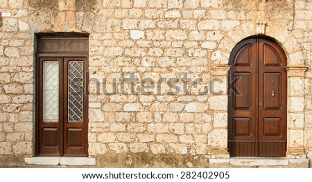 Stone wall with two doors. The wall of an old house in Europe with the front door. Background texture of large stone bricks. Ancient wooden door in stone castle wall. Southern Italy. Europe. - stock photo