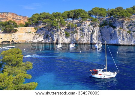 Stone walls above white sail boats on the calanques near Cassis, France - stock photo