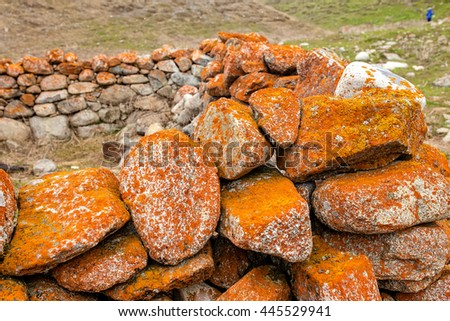 stone walls of ancient homes in the mountains - stock photo
