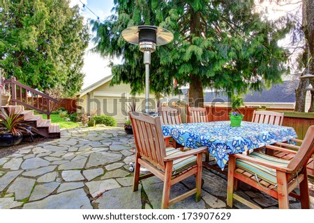 Stoned patio area with wood dining table set, heat lamp - stock photo
