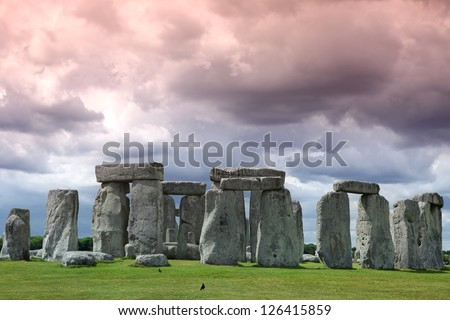 Stonehenge historic site on green grass under cloud sky. Stonehenge is a UNESCO world heritage site in England with origins estimated at 3,000BC