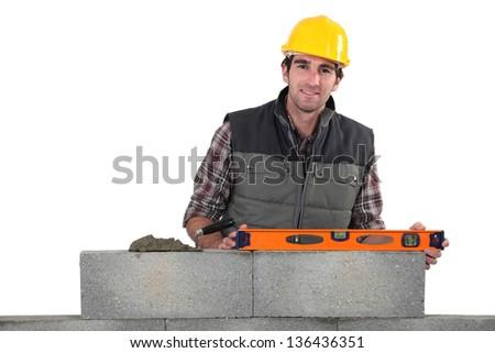 Stonemason using a bubble level - stock photo