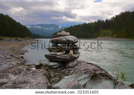 stones are piled on the river Bank in the balance against Dark Ominous Sky