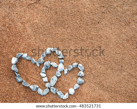 Stones arranged to form a heart on the sand .