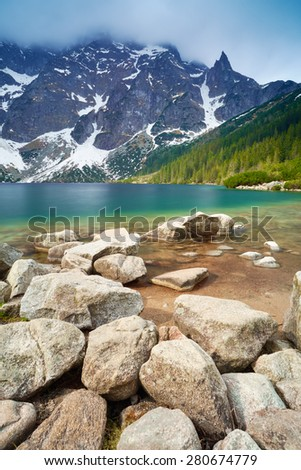 Stones at a shore of the Morskie Oko lake in the High Tatra Mountains. Carpathians, Poland - stock photo