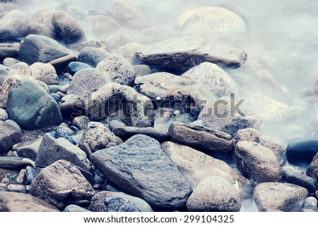 Stones at sea shoreline. Color filtered imaged. - stock photo