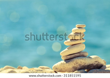 Stones balance at the vintage beach, inspirational summer landscape. Stability hierarchy stack over blue sea in Croatia. Spa or well-being, freedom and stability concept on rocks. - stock photo