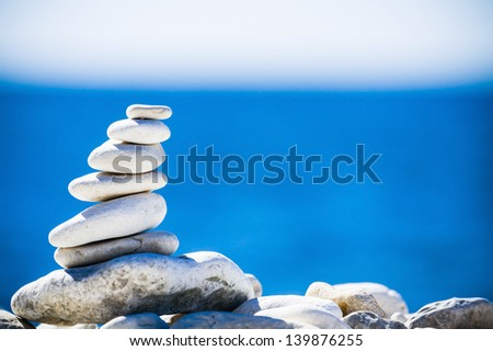 Stones balance, hierarchy stack over blue sea in Croatia. Spa or well-being, freedom and stability concept on rocks. - stock photo