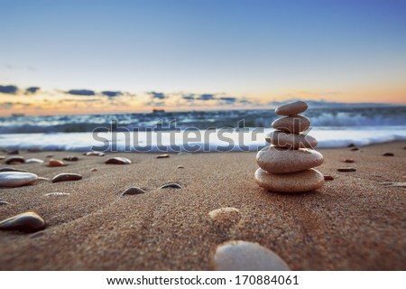 Stones balance on beach, sunrise shot  - stock photo