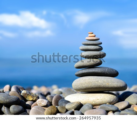Stones balance, pebbles stack over blue sea in Crimea. Blue sky on sunny  coast in summer. - stock photo