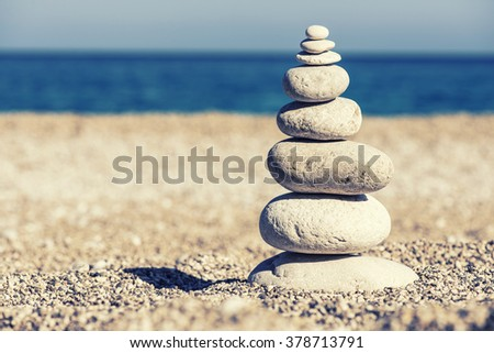 Stones balance, vintage retro instagram like hierarchy stack over blue sea background. Spa or well-being, freedom and stability concept on rocks. - stock photo