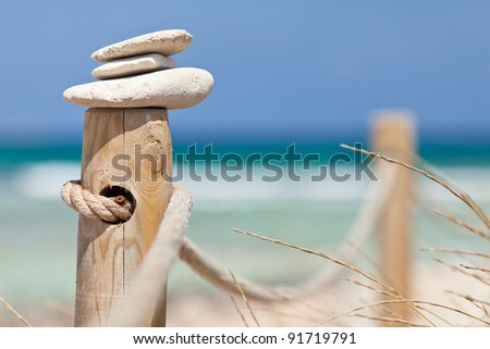 Stones balanced on wooden banister near the Trucadors beach.  Formentera island, Spain. - stock photo