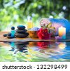stones candle camellia oil salt towel on water - stock photo