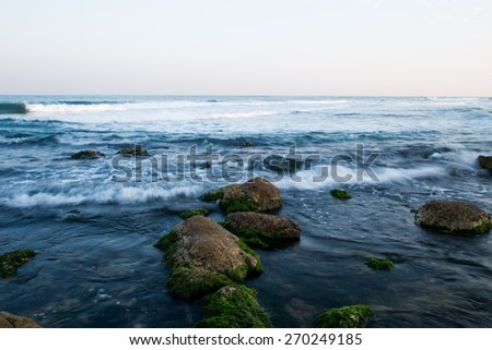 Stones in a sea with waves. - stock photo
