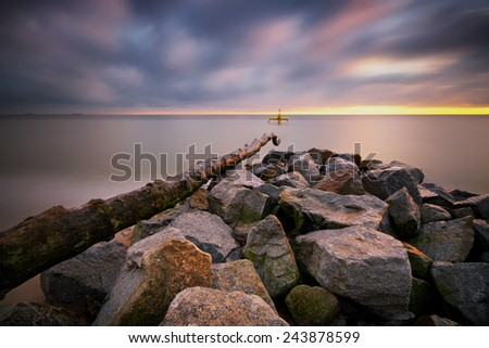 stones in sea water on the background of sunrise - stock photo