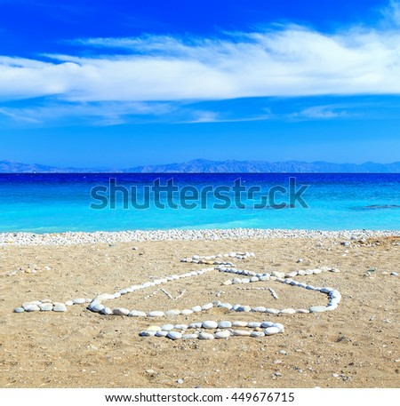 stones in shape of heart on pebble beach. the Aegean Sea islands and clouds background