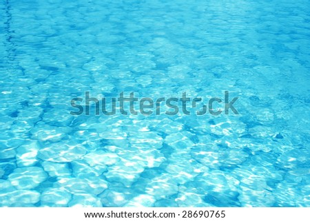 Stones in the blue water. - stock photo