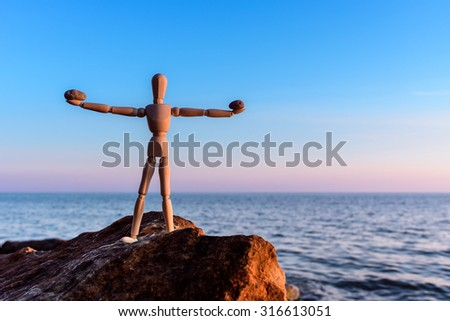 Stones in the hands of a wooden mannequin - stock photo