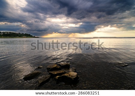 Stones in the lake and gloomy clouds - stock photo