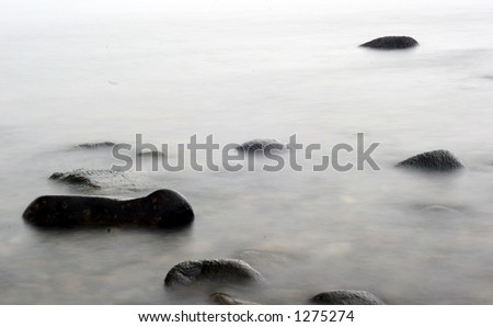 stones in the water in denmark on the north coast of the seeland island, slow shutter speed