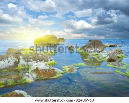 stones into the sea on sunny sky background