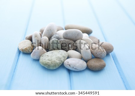 Stones isolated on wood background. Pile of white stones on a blue smooth wooden table - stock photo