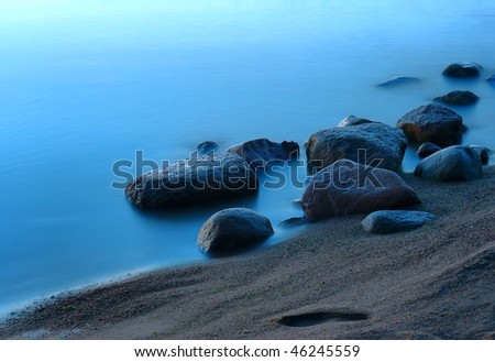 Stones lying on the beach and washed with water in a white night.