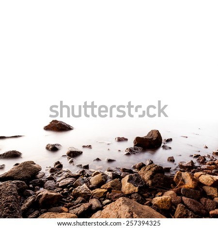 Stones on a background of blurred sea on the white backgrounds - stock photo