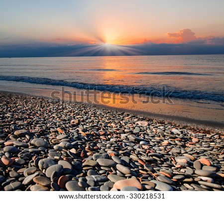 Stones on beach and sea water - stock photo