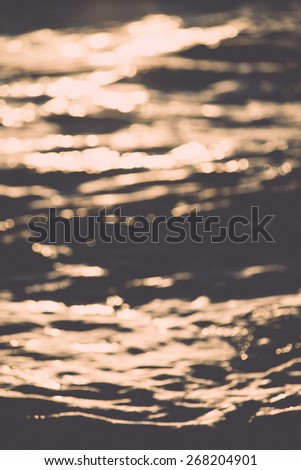 Stones on beach and sea water in sunset light - retro vintage film effect - stock photo