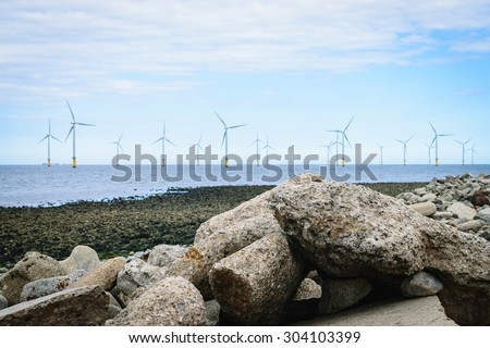 Stones on the beach and blur wind turbine background