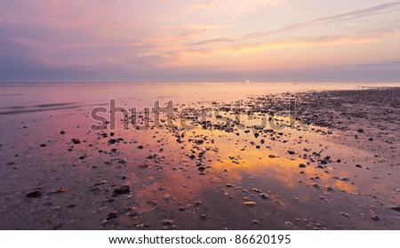 stones on the beach at sunset - stock photo