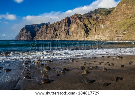 Stones on the Beach of Ocean Coast during Sunset - Los Gigantes, Tenerife, Canary Islands, Spain - stock photo