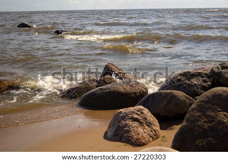 stones on the beach of the Gulf of Finland in bright summer day - stock photo