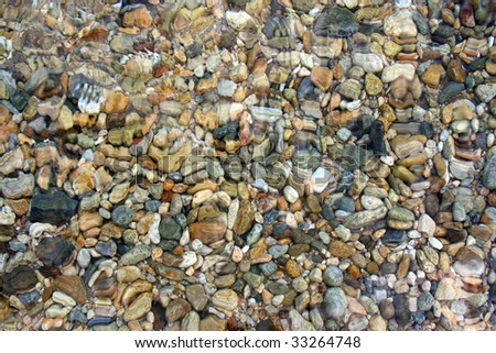stones on the ground of clear water - stock photo
