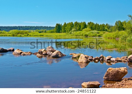 Stones on the river on a background of a wood - stock photo