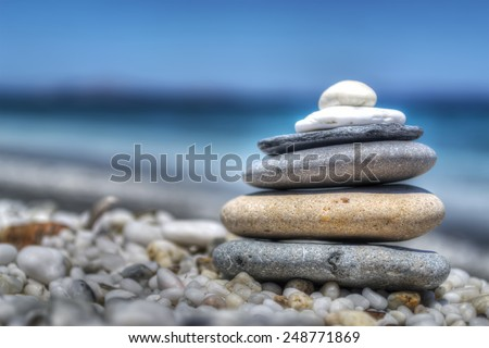 stones pile on white pebbles by the shore. Processed for hdr tone mapping effect