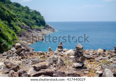 Stones pyramid on mountain and sea