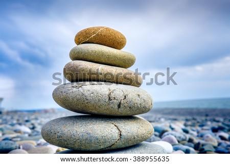 Stones pyramid on pebble beach symbolizing stability, zen, harmony, balance. - stock photo