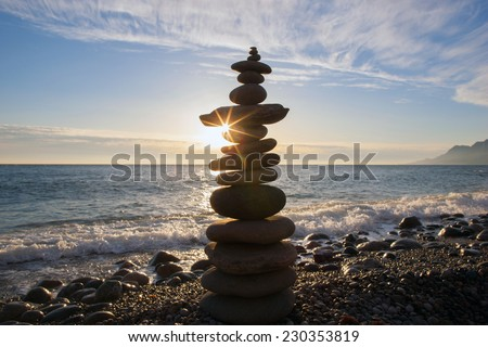 Stones pyramid on sand symbolizing zen, harmony, balance. Ocean at sunset - stock photo