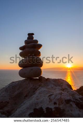 Stones pyramid on sand symbolizing zen, harmony, balance. Ocean at sunset - stock photo