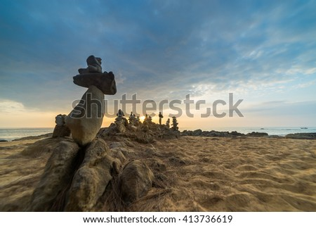 Stones pyramid on sand symbolizing zen, harmony, balance. Ocean at sunset in Khao Lak Thailand - stock photo