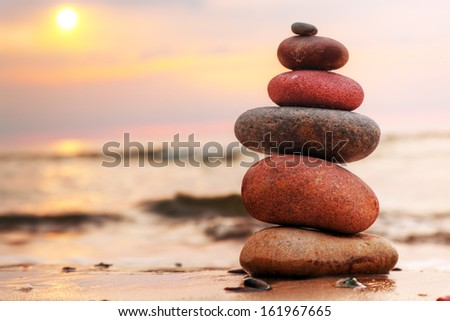 Stones pyramid on sand symbolizing zen, harmony, balance. Ocean at sunset in the background - stock photo