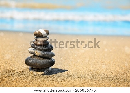 Stones pyramid on sand symbolizing zen, harmony, balance. Ocean in the background  - stock photo